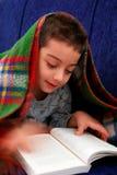 El muchacho lee el libro debajo de la manta Imagen de archivo