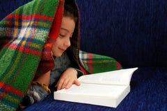 El muchacho lee el libro debajo de la manta Imágenes de archivo libres de regalías
