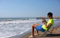 El muchacho lee un ebook en la costa Imágenes de archivo libres de regalías