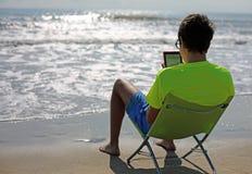 El muchacho lee un ebook que se sienta en la silla de playa Imagen de archivo