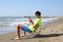 El muchacho lee un ebook que se sienta en la silla de playa en los wi de la costa Imagen de archivo libre de regalías