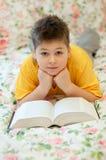 el muchacho lee un libro en cama Foto de archivo