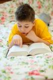 El muchacho lee un libro en cama Foto de archivo libre de regalías