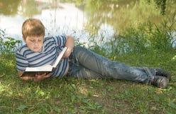 El muchacho lee un libro grande imágenes de archivo libres de regalías