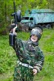 El muchacho levanta la mano con el arma del paintball imágenes de archivo libres de regalías