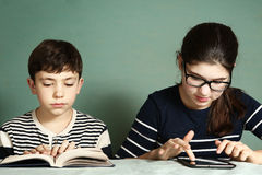 El muchacho leyó juegos de tableta del juego de la muchacha del libro Foto de archivo