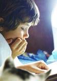 El muchacho leyó el libro en cama con el gato Fotos de archivo