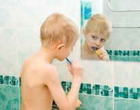 El muchacho limpia los dientes en un baño Fotos de archivo
