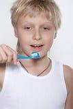 El muchacho limpia los dientes un cepillo de dientes. Foto de archivo libre de regalías
