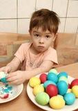 El muchacho limpia los huevos de Pascua Imágenes de archivo libres de regalías