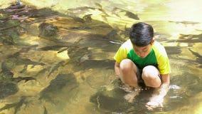 El muchacho lindo asiático joven se sienta y juega en el río metrajes