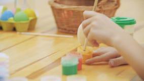 El muchacho lindo colorizing un huevo de Pascua en un color amarillo con una ayuda de la brocha El muchacho dibuja un corazón ama