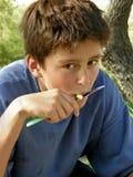 El muchacho lindo come una manzana con un cuchillo Fotos de archivo libres de regalías