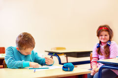 El muchacho lindo con el special necesita escribir letras mientras que se sienta en el escritorio en sitio de clase Imagenes de archivo