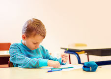 El muchacho lindo con el special necesita escribir letras mientras que se sienta en el escritorio en sitio de clase Imagen de archivo