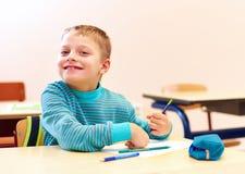 El muchacho lindo con el special necesita escribir letras mientras que se sienta en el escritorio en sitio de clase Foto de archivo