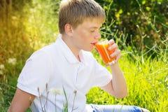 El muchacho lindo con las pecas es vidrio de consumición de la zanahoria Fotografía de archivo libre de regalías