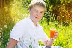 El muchacho lindo con las pecas está sosteniendo el vidrio de la naranja Fotos de archivo