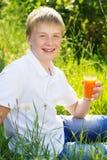 El muchacho lindo con las pecas está sosteniendo el vidrio de la zanahoria Foto de archivo libre de regalías
