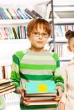 El muchacho lindo con los vidrios sostiene los libros en biblioteca Foto de archivo libre de regalías