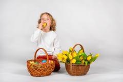 El muchacho lindo con el pelo ondulado se sienta en un fondo blanco al lado de una cesta con los huevos de Pascua imagen de archivo
