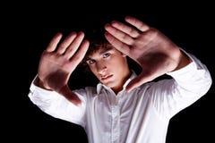 El muchacho lindo con sus manos levantó Imagen de archivo
