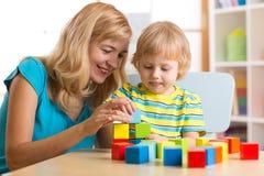 El muchacho lindo de la madre y del niño juega así como los juguetes educativos Foto de archivo