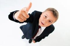 El muchacho lindo del adolescente en la camisa blanca y el lazo que señalaban con su finger en un blanco aislaron el fondo Fotografía de archivo libre de regalías