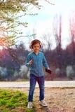 El muchacho lindo del niño con los auriculares escucha la música y el baile en parque floreciente Imagen de archivo