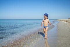 El muchacho lindo del niño está corriendo en el mar Imágenes de archivo libres de regalías