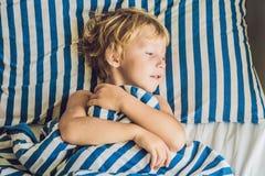 El muchacho lindo despertó en su cama Concepto del sueño de los niños imagenes de archivo