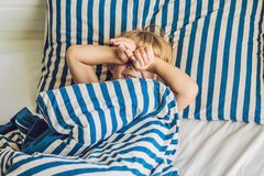 El muchacho lindo despertó en su cama Concepto del sueño de los niños foto de archivo libre de regalías