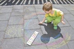 El muchacho lindo dibuja con tizas coloridas en el asfalto Actividad del verano y juegos creativos para los pequeños niños Niño j foto de archivo
