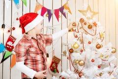 El muchacho lindo en el sombrero rojo de santa adorna un árbol del Año Nuevo Fotos de archivo