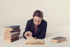 El muchacho lindo en un traje miente y leyendo un libro en un fondo gris Imagen de archivo