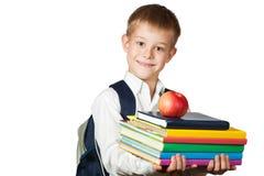 El muchacho lindo es libros y manzana de la explotación agrícola. aislado Imagen de archivo