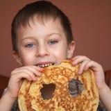 El muchacho lindo está comiendo la crepe Fotografía de archivo libre de regalías