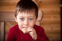 El muchacho lindo está comiendo la oblea Imagenes de archivo