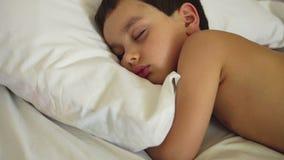 El muchacho lindo está durmiendo en una cama almacen de metraje de vídeo