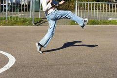 El muchacho lindo está golpeando la bola en el patio Fotos de archivo