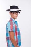 El muchacho lindo está presentando con el casquillo y gafas Fotografía de archivo