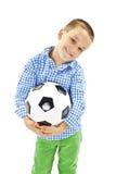 El muchacho lindo está sosteniendo una bola del fútbol hecha del cuero auténtico Balón de fútbol Fotos de archivo libres de regalías