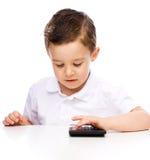 El muchacho lindo está utilizando la calculadora Imagen de archivo libre de regalías