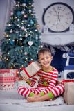 El muchacho lindo feliz del pequeño niño se vistió en los pijamas rayados que se sentaban en sitio adornado de Año Nuevo en casa Fotos de archivo libres de regalías