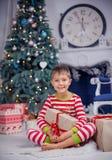 El muchacho lindo feliz del pequeño niño se vistió en los pijamas rayados que se sentaban en sitio adornado de Año Nuevo en casa Foto de archivo