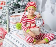 El muchacho lindo feliz del pequeño niño se vistió en los pijamas rayados que se sentaban en sitio adornado de Año Nuevo en casa Fotografía de archivo