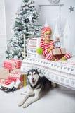 El muchacho lindo feliz del pequeño niño se vistió en los pijamas rayados que se sentaban en sitio adornado de Año Nuevo en casa Fotografía de archivo libre de regalías