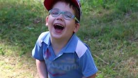 El muchacho lindo feliz en vidrios y casquillo ríe almacen de metraje de vídeo