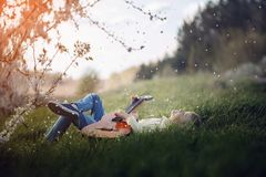 El muchacho lindo miente en la hierba con una guitarra en puesta del sol Fotografía de archivo