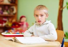 El muchacho lindo, niño con el special necesita aprender en centro de rehabilitación Imagenes de archivo